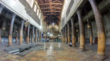 local de nascimento : Church of the Nativity interior with hall colonnade, altar and icon lamps hanging on long chain in Bethlehem timelapse hyperlapse.
