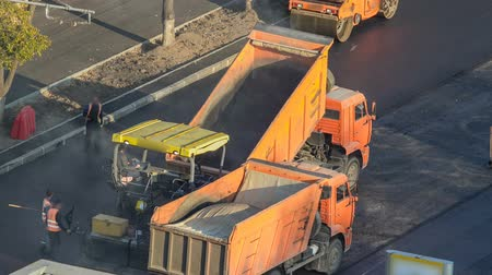 bitume : Workers operating asphalt paver machines during road construction and repairing works timelapse Vidéos Libres De Droits
