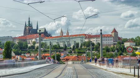 hradcany : Red tram passing on Manes Bridge timelapse Manesuv Most and famous Prague Castle on the background in Prague, Czech Republic.