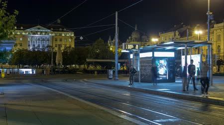 скольжение : New modern trams of Croatian capital Zagreb night timelapse near railway station. ZAGREB, CROATIA Стоковые видеозаписи