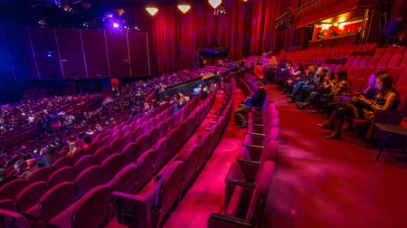 teatral : Spectators gather in the auditorium and watch the show in theatre timelapse. Large hall with red armchairs seats