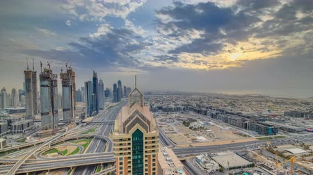 metro : Dubai skyline timelapse at sunset with beautiful city center skyscrapers and Sheikh Zayed road traffic, Dubai, United Arab Emirates
