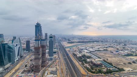 prestiž : Dubais business bay towers before sunset timelapse. Rooftop view of some skyscrapers and new towers under construction.