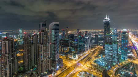 prestiž : Dubai business bay towers illuminated at night timelapse. Rooftop view of some skyscrapers and new towers under construction.