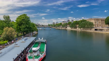 Touristic boat passes below Pont des Arts and stop on boat station on Seine river timelapse hyperlapse in Paris.