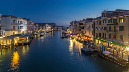 olasz kultúra : Grand Canal in Venice, Italy day to night timelapse. View on gondolas and city lights from Rialto Bridge. Stock mozgókép