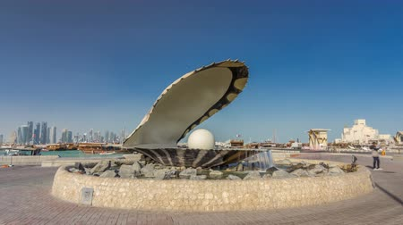 oysters : A fountain featuring an oyster with a gigantic pearl inside timelapse hyperlapse with the Doha skyline behind it
