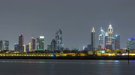 ОАЭ : Modern Dubai city skyline timelapse at night with illuminated skyscrapers over water surface