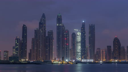 スクレーパー : Panorama of modern skyscrapers in Dubai city night to day timelapse from the Palm Jumeirah Island.