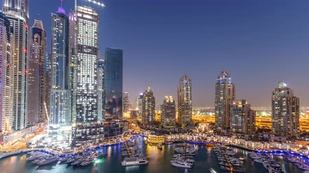 lavish : Dubai Marina skyscrapers aeral day to night timelapse, port with luxury yachts and marina promenade