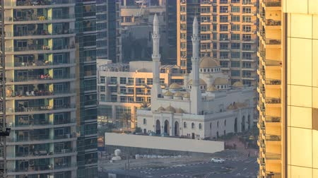 fascinante : Al Raheem mosque between skyscrapers timelapse on the marina walk in Dubai Marina, Dubai, UAE.