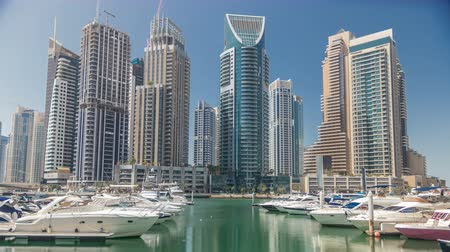 motorbot : Panoramic view with modern skyscrapers and water pier with yachts of Dubai Marina timelapse, United Arab Emirates