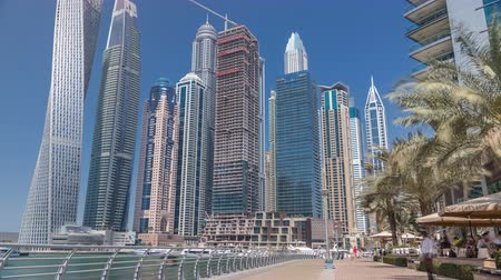 middle : Panoramic view with modern skyscrapers and yachts of Dubai Marina timelapse, United Arab Emirates