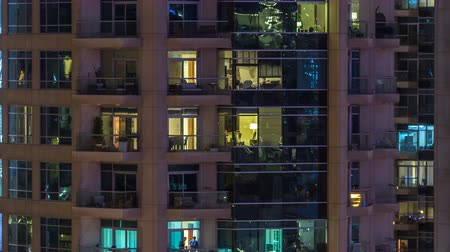 занятость : Windows of the multi-storey building of glass and steel lighting inside and moving people within timelapse
