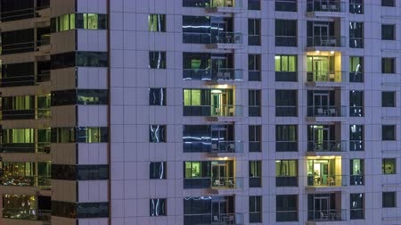 diferença : Windows of the multi-storey building of glass and steel lighting inside and moving people within timelapse
