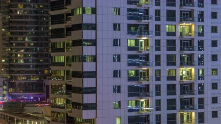 within : Windows of the multi-storey building of glass and steel lighting inside and moving people within timelapse