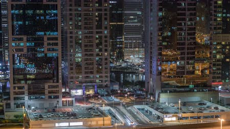tramwaj : Aerial view of Jumeirah lakes towers skyscrapers night timelapse with traffic on sheikh zayed road.