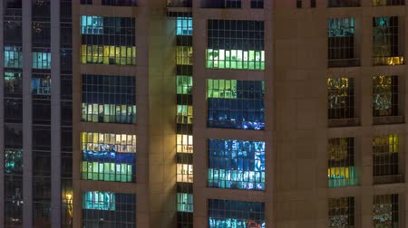 pisos exteriores : Windows of the multi-storey building of glass and steel lighting inside and moving people within timelapse