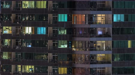 built up : Windows of the multi-storey building of glass and steel lighting inside and moving people within timelapse