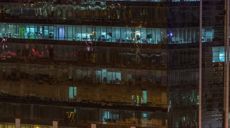 штаб квартира : Windows of the multi-storey building of glass and steel lighting inside and moving people within timelapse