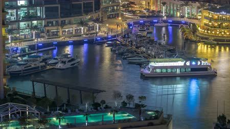 torony : Promenade and canal in Dubai Marina with luxury skyscrapers and yachts around night timelapse, United Arab Emirates Stock mozgókép