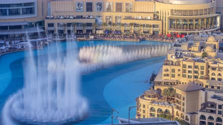 largest city : Evening aerial view Dancing fountains downtown and in a man-made lake timelapse in Dubai, UAE.