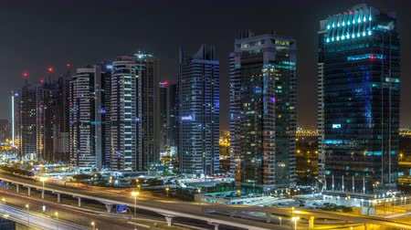 metro : Aerial view of Jumeirah lakes towers skyscrapers during all night timelapse with traffic on sheikh zayed road.