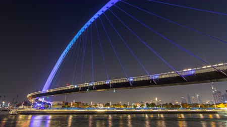 yaya köprüsü : Futuristic Pedestrian Bridge over the Dubai Water Canal Illuminated at Night timelapse hyperlapse, UAE.