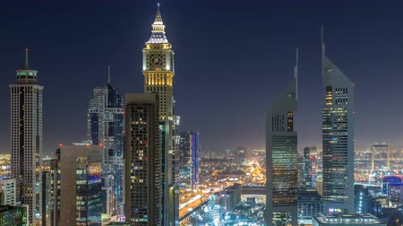 недвижимость : Skyline view of the buildings of Sheikh Zayed Road and DIFC night timelapse in Dubai, UAE.