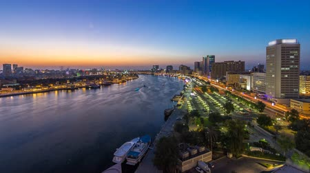 emirados : Dubai creek landscape day to night timelapse with boats and ship near waterfront