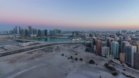 binário : Aerial skyline of Abu Dhabi city centre from above day to night timelapse