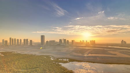dredging : Buildings on Al Reem island in Abu Dhabi at sunset timelapse from above. Stock Footage