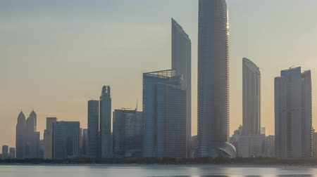 capitello : Abu Dhabi city skyline with skyscrapers after sunrise with water reflection timelapse