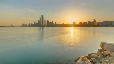 ОАЭ : Abu Dhabi city skyline on sunrise time with water reflection timelapse. Стоковые видеозаписи