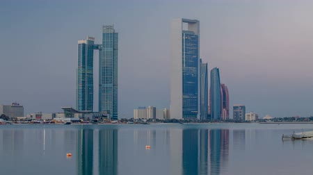 corniche : Abu Dhabi city skyline with skyscrapers before sunrise with water reflection night to day timelapse
