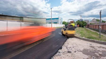 macadam : A paver finisher, asphalt finisher or paving machine placing a layer of asphalt during a repaving construction project timelapse Stock Footage