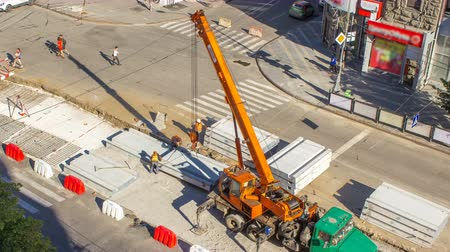miktar : Installing concrete plates by crane at road construction site timelapse.