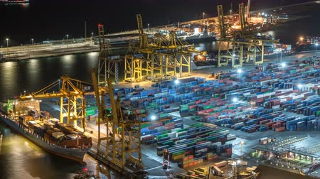 serial : Seaport and loading docks at the port with cranes and multi-colored cargo containers night timelapse Stock Footage