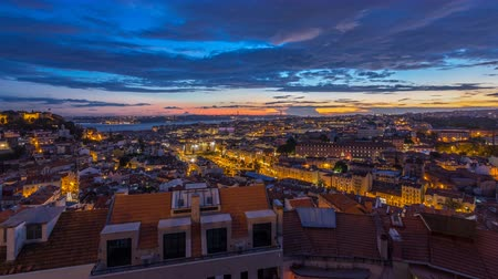 miradouro : Lisbon after sunset aerial panorama view of city centre with red roofs at Autumn day to night timelapse, Portugal