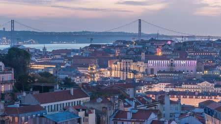 alfama : Lisbon after sunset aerial panorama view of city centre with red roofs at Autumn day to night timelapse, Portugal