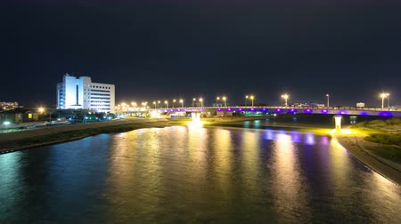 ural : Modern houses and illuminated bridge on the riverside Ural in city Atyrau timelapse hyperlapse Stock Footage
