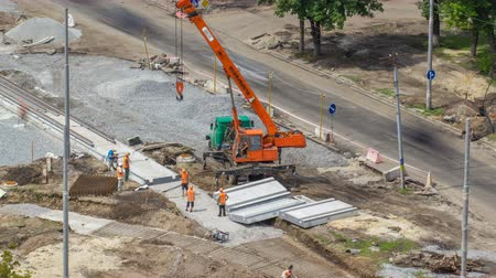 rekonstrukce : Installing concrete plates by crane at road construction site timelapse.