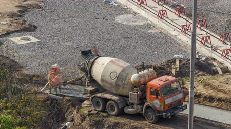roadworks : Concrete works for road construction with many workers and mixer timelapse