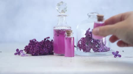 пробирка : Someone hand placing lilac essence in glass vial, with fresh lilac flowers