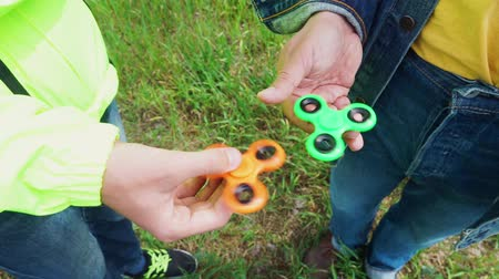 trendy fidget spinner - two persons holding spinning green and orange fidget spinners in hands