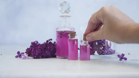 homeopathic : Someone hand placing corc in lilac essence in glass vial, with fresh lilac flowers