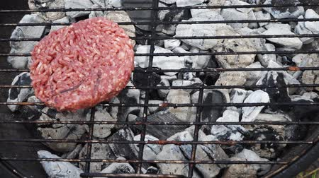 BBQ gill with hamburgers - preparing beef burgers outdoor, placing raw burgers on grill