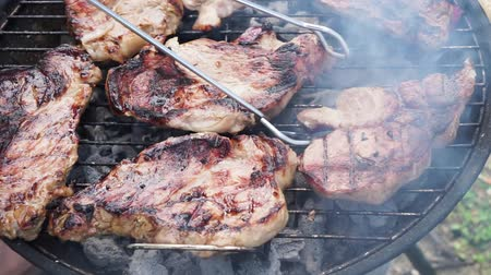 BBQ with meat steaks, checking if meat is ready Стоковые видеозаписи