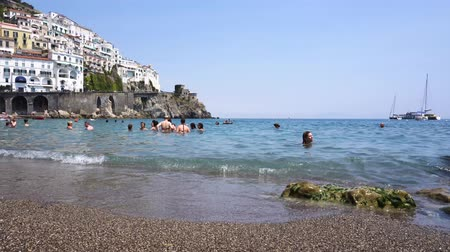 солнечные ванны : AMALFI, ITALY - JULY 14, 2017: People enjoying sea at Amalfi town beach and Tyrrhenian sea waters, Italy Стоковые видеозаписи
