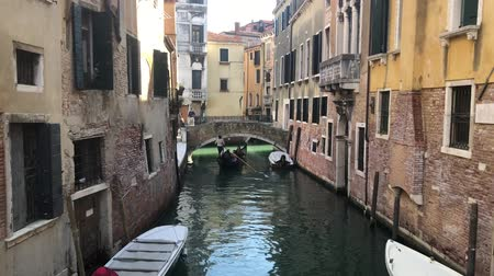 venezia : VENICE, ITALY - MARCH 28, 2018: people takin stroll in gondola at traitional Venice canal with reflection of houses, Italy